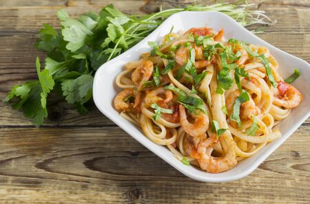 spaghetti with prawns in tomato sauce with herbs. traditional Italian cuisine.
