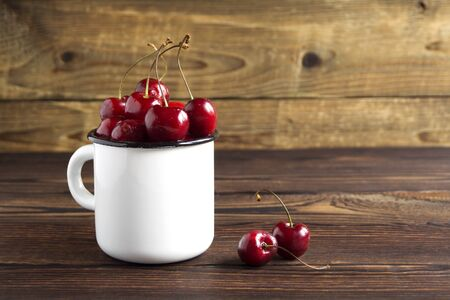 ripe fresh cherries in a mug on a wooden background. Reklamní fotografie