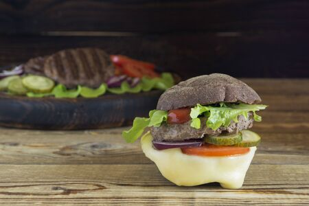 homemade Burger with rye bun. on a wooden background.