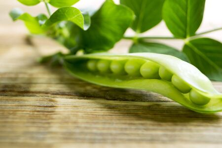 pods of young green peas on a wooden background. Reklamní fotografie