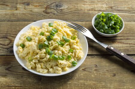 scrambled eggs on a white plate with green onions. on a wooden background. Reklamní fotografie