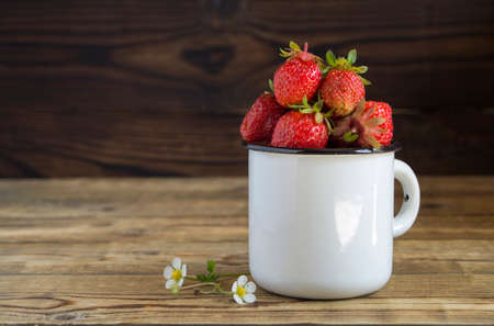 ripe fresh strawberries in a mug. on a wooden background