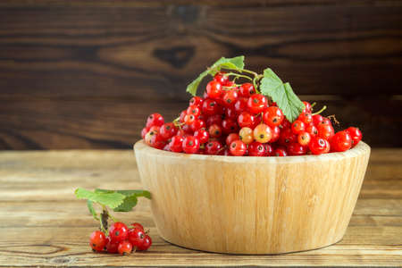ripe red currants in a bamboo bowl. on a wooden background