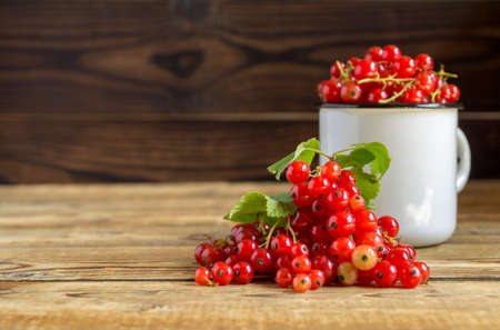 ripe red currants in a Cup. on a wooden background
