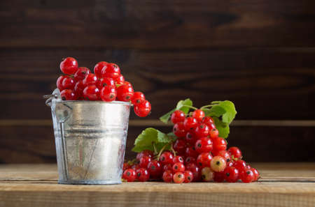 ripe red currants on a wooden background