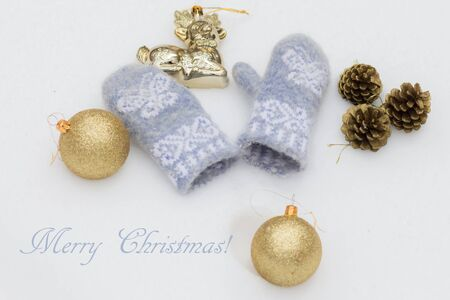 balls decorated: Christmas toys golden shiny balls, decorated with fir cones and baby blue woolen mittens on the white snow. With beautiful inscription Merry Christmas