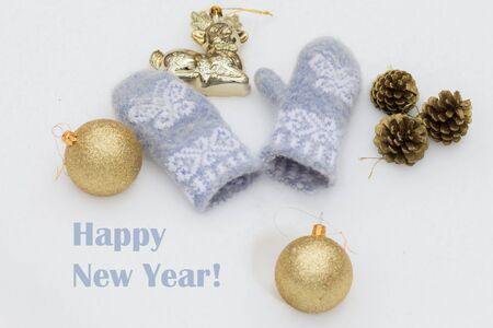 balls decorated: Christmas toys golden shiny balls, decorated with fir cones and baby blue woolen mittens on the white snow. With beautiful inscription Happy New Year