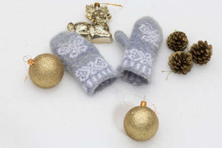 balls decorated: Christmas toys golden shiny balls, decorated with fir cones and baby blue woolen mittens on the white snow