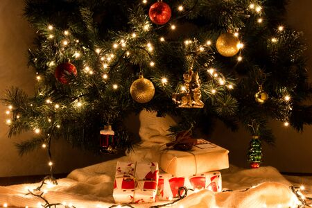 christmas tree presents: Christmas presents under decorated gerlyandoy, bright yellow and red balls Christmas tree