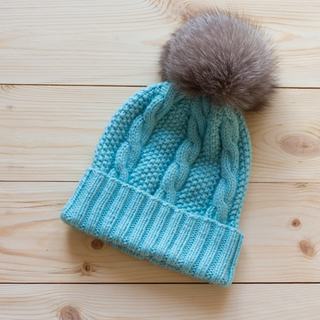 pompon: blue cap wool connected manually with a fur pompon of arctic fox on a natural wooden background