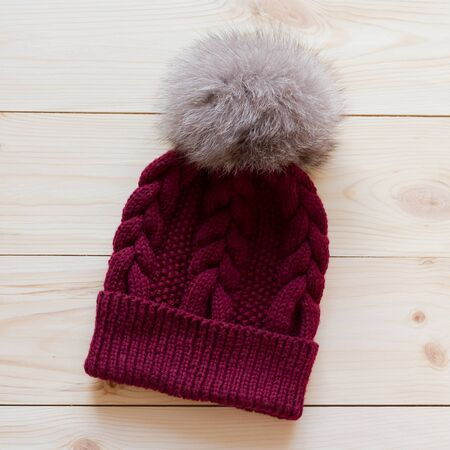 arctic fox: blue cap wool connected manually with a fur pompon of arctic fox on a natural wooden background