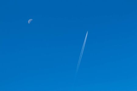 reversing: Plane in a clear sky, reversing the track from him and half moon