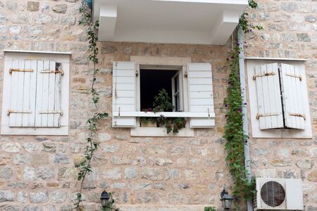 open windows: Open Window with flowers and two closed windows with white shutters on a stone wall