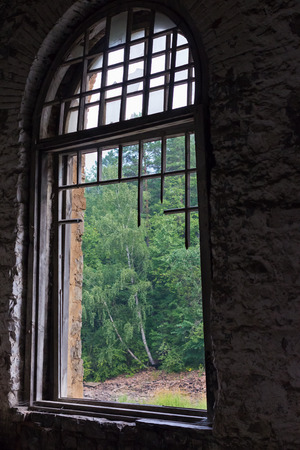 without window: The old large window without glass, with a broken wooden frame, with views of the forest Stock Photo