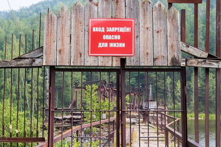 life threatening: rusty iron fence on the dam and the inscription in Russian Trespassing! Life threatening Stock Photo