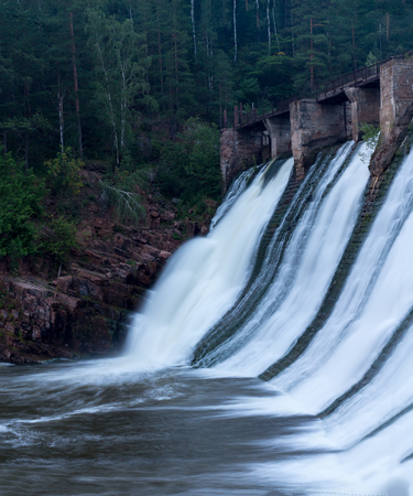 Water flowing down the walls of the old small hydropower plants Stock Photo