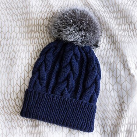 blue knitted cap with fur pompon