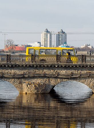 water bus: yellow bus on a stone bridge over the river