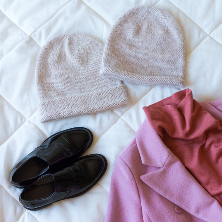 Beige hats, pink cashmere coat, red sweater and black patent leather shoes
