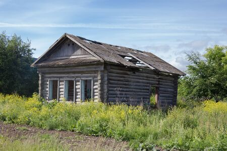 damaged roof: A crumbling old house made of logs without Windows and a leaky roof Stock Photo