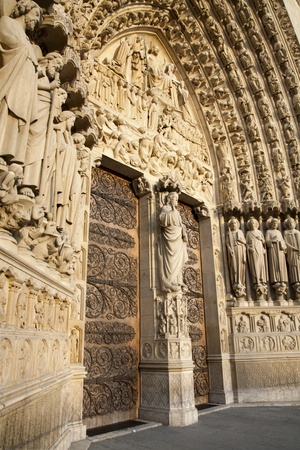 religiosity: Paris - main portal of Notre-Dame cathedral in the sunset light
