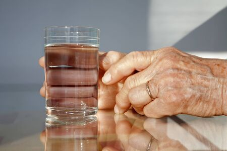 senescence: hands of old woman and glass of water