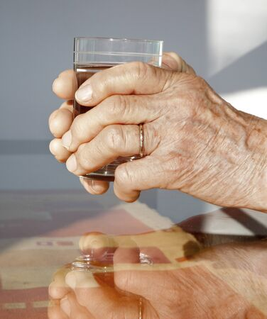 hands of old woman and glass of water
