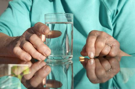 hands of old woman with a pill and water photo