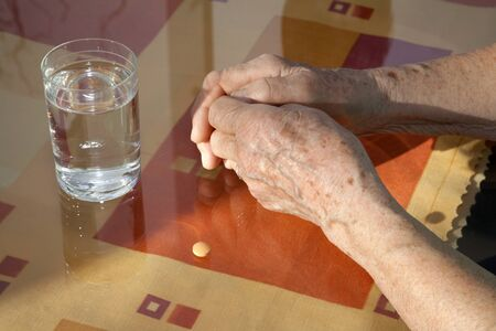 senescence:  hands of old woman and glass of water Stock Photo
