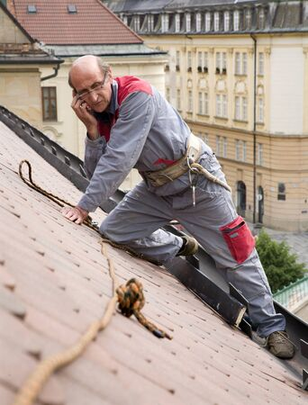 man at work and calling on the roof  photo