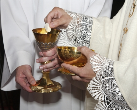 hand of catholic priest by communion