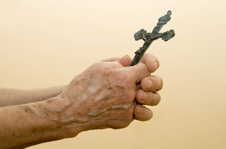 religiosity: hand of old woman with the cross