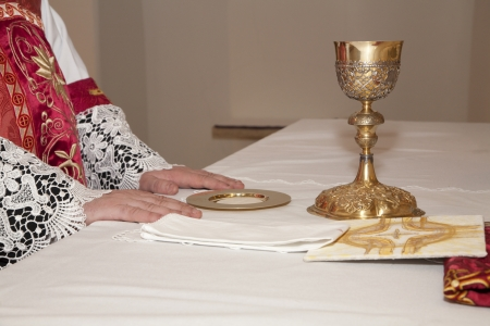 religiosity: hands of priest by the mass and the cap