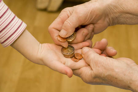 senescence: hands of grandmother and grandchild with money