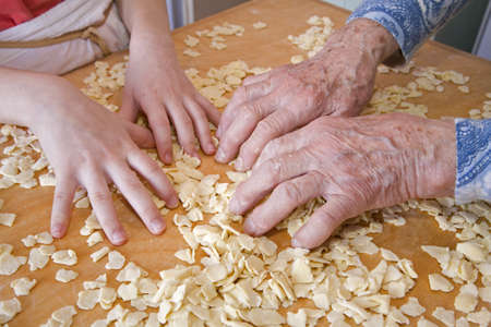 senescence:  hands of grandmother and grandchilds at cooking