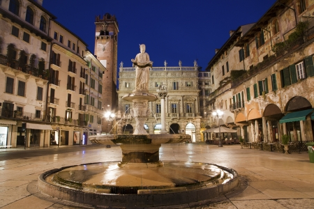 Verona - Fountain on Piazza Erbe in dusk and Porta Leona and Palazzo Maffei in backgroud