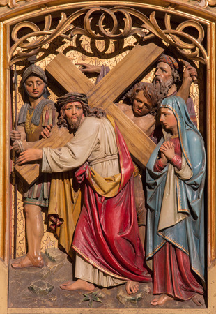 BRATISLAVA, SLOVAKIA - JANUARY 14, 2014: Jesus under cross meets his mother. Carved relief from 19. cent.  by Ferdinand Prinoth from St. Ulrich on gothic side altar in st. Martin cathedral.