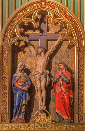 BRATISLAVA, SLOVAKIA - JANUARY 14, 2014: Crucifixion scene. Carved sculptures from 19. cent by Ferdinand Prinoth from St. Ulrich  on gothic side altar in st. Martin cathedral.