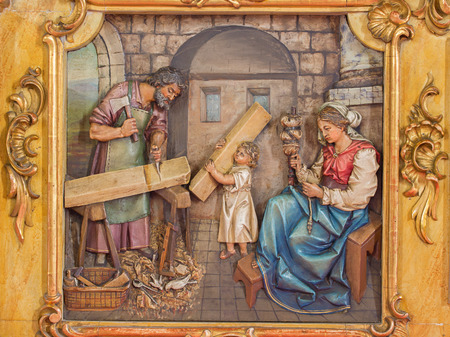 TRNAVA, SLOVAKIA - MARCH 3, 2014: Carved relief of Holy family in workroom from side altar of st. Joseph in Jesuits church from 19. cent.