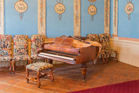 anton: SAINT ANTON, SLOVAKIA - FEBRUARY 26, 2014: Piano in music saloon in palace Saint Anton with the handmade needlework on the chairs from 19. cent.