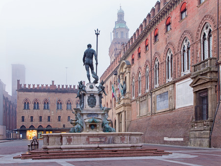 Bologna - Fontana di Nettuno or Neptune fountain on Piazza Maggiore square and Palazzo Comunale in fogy morning Stock Photo