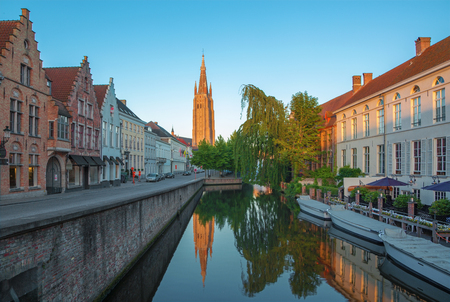 Bruges - Look to canal from Sint Jan Nepomucenus bridge with the tower of Our Lady church in morning light.