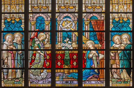 BRUGES, BELGIUM - JUNE 12, 2014: The Annunciation on windowpane in St. Salvators Cathedral (Salvatorskerk) by stained glass artist Samuel Coucke (1833 - 1899)
