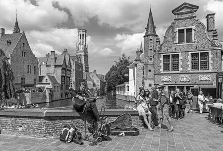 belfort: Brugge - View from the Rozenhoedkaai in Brugge with the street musician and the Perez de Malvenda house and Belfort van Brugge in the background. Editorial