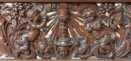 eucharist: BRUGES, BELGIUM - JUNE 13, 2014: Carved relief of angel and cup as the symbol of eucharist in Karmelietenkerk (Carmelites church) by carmelite Victor van de Heilige Jacob from 17. cent.