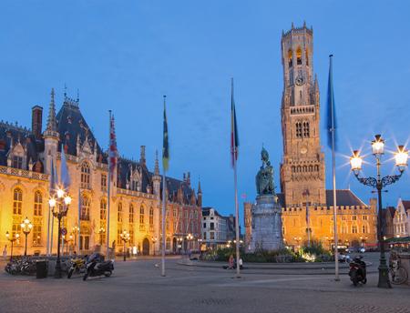 belfort: BRUGES, BELGIUM - JUNE 13, 2014: Grote markt in evening dusk. Belfort van Brugge and Provinciaal Hof buildings and and memorial of Jan Breydel and Pieter De Coninck