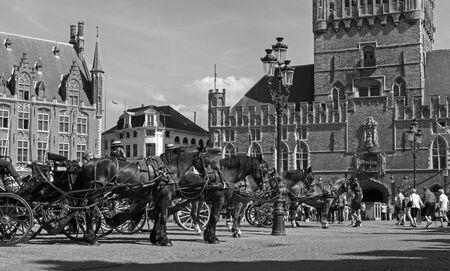 belfort: BRUGGE, BELGIUM - JUNE 12, 2014: The Carriage on the Grote Markt and Belfort van Brugge in background.