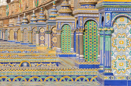mudejar: SEVILLE, SPAIN - OCTOBER 28, 2014: The tiled Province Alcoves along the walls of the Plaza de Espana (1920s) by Domingo Prida.