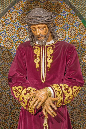 vested: SEVILLE, SPAIN - OCTOBER 28, 2014: The tradicional vested Jesus Christ statue in bond in church Iglesia de San Pedro.