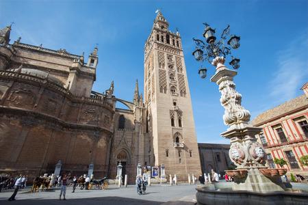 SEVILLE, SPAIN - OCTOBER 28, 2014: Cathedral de Santa Maria de la Sede with the Giralda bell tower from Plaze del Triumfo.